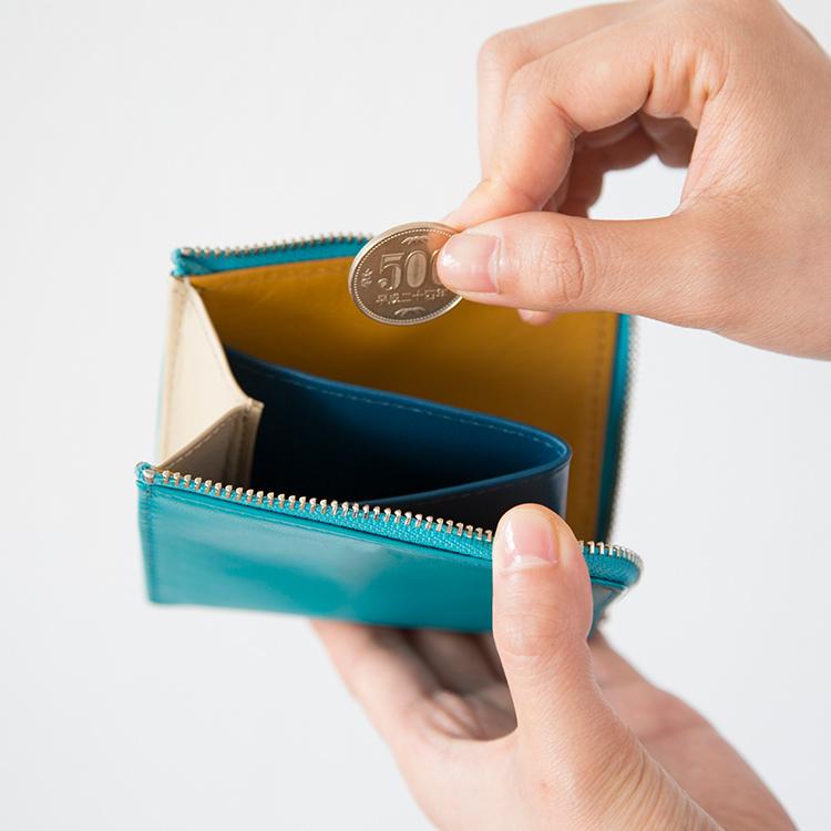 コンパクトウォレットを開いてコインを入れようとしている写真